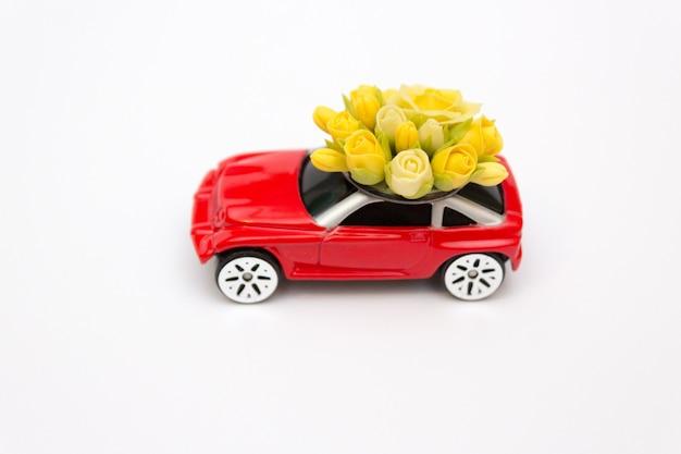Czerwony zabawkarski samochód, kwiat dostawa, walentynka dzień, pojęcie