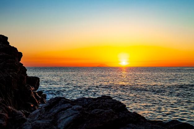 Czerwony zachód słońca nad morzem. piękny zachód słońca. zachód słońca nad morzem tyrreńskim w kalabrii we włoszech.
