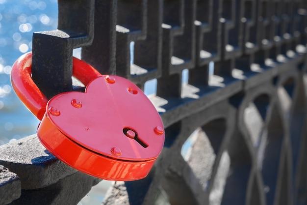 Czerwony zamek miłości na metalowej siatce