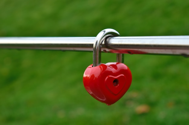 Czerwony zamek serca wisi na metalowej poręczy. blokada serca jest znakiem wiecznej miłości.