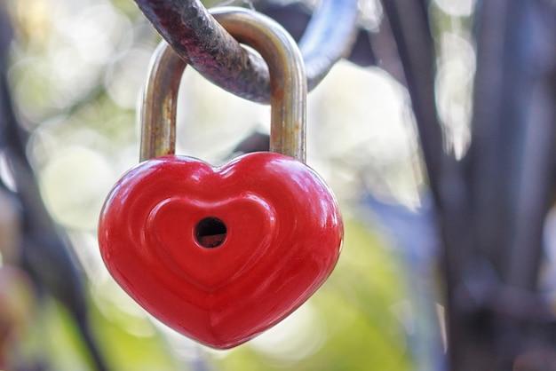 Czerwony zamek w kształcie serca wisi na żelaznej szynie.