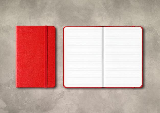 Czerwony zamknięte i otwarte notebooki pokryte na białym tle na tle betonu