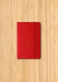 Czerwony zamknięty notatnik na białym tle na powierzchni drewnianych