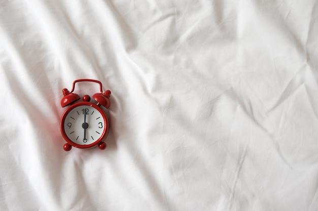 Czerwony zegar analogowy na białej pogniecionej pościeli. widok z góry, leżał płasko, miejsce. poziomy.