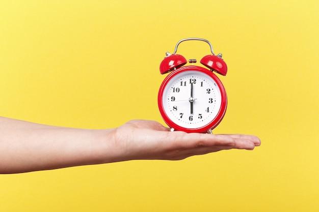 Czerwony zegar z budzikiem pod ręką