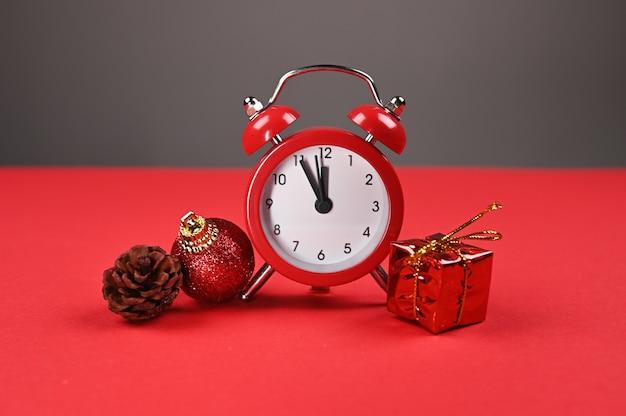 Czerwony zegarek i opakowanie na prezent na czerwonym tle.