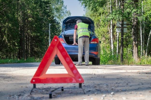 Czerwony znak ostrzegawczy stoi na poboczu drogi obok uszkodzonego pojazdu