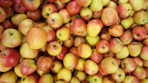 Czerwony żółty jabłka tło w stosie świeże jabłczane owoc
