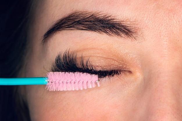 Czesanie przedłużonych rzęs. kobieta oko z pięknym makijażem i długimi rzęsami. pędzel do tuszu do rzęs. zabieg pielęgnacyjny rzęs: lifting, barwienie, podkręcanie, laminowanie i przedłużanie rzęs.