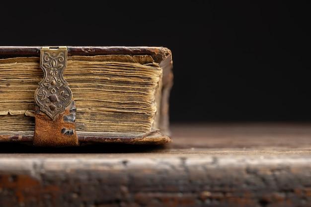 Część antycznej książki na zapięciu jest widoczna na starym drewnianym stole zbliżenie