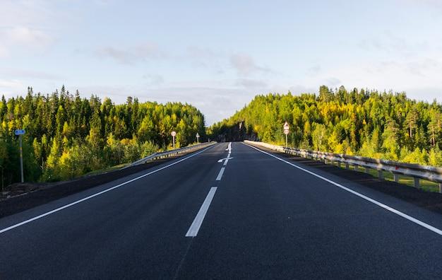 Część autostrady latem. wzdłuż lasu mieszanego. z widokiem na niebo