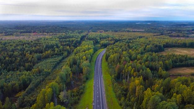 Część autostrady we wrześniu. wzdłuż lasu mieszanego. z widokiem na niebo. widok z góry