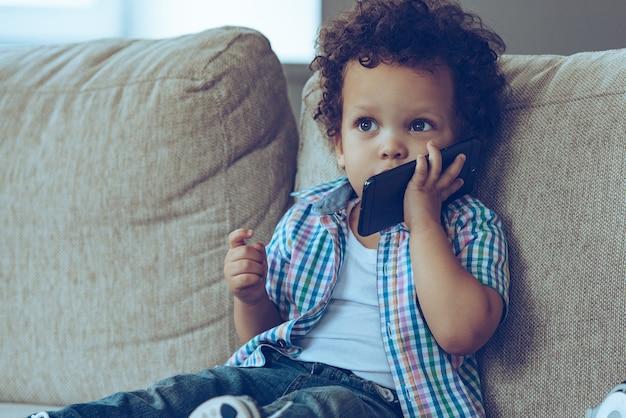 Cześć babciu! mały afrykański chłopiec rozmawia przez telefon komórkowy i odwraca wzrok, siedząc na kanapie w domu