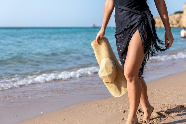 Część ciała kobiety spacerującej brzegiem morza w upalny letni dzień.