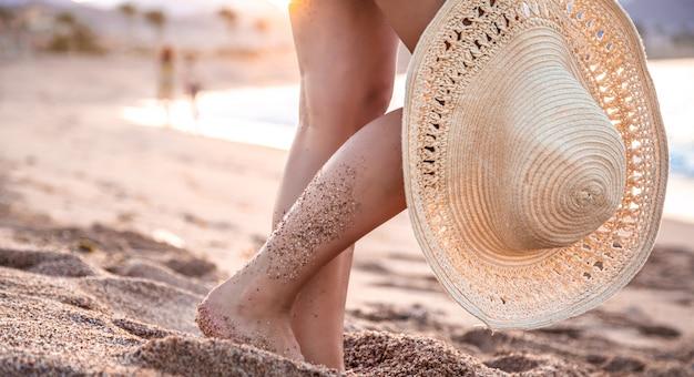 Część ciała. stopy kobiety stojącej na plaży o zachodzie słońca w kapeluszu.