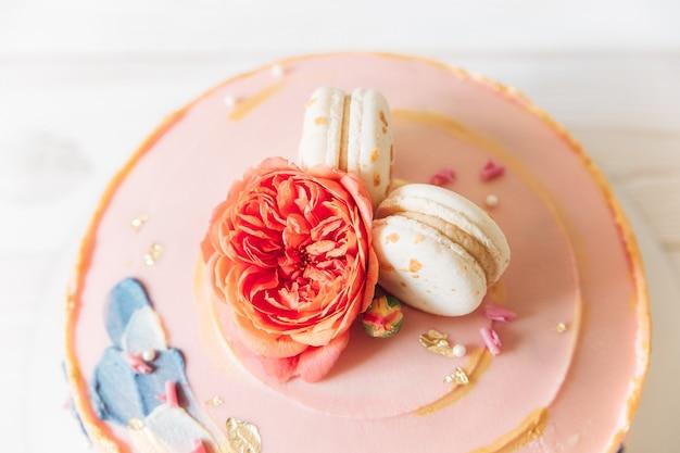 Część ciasta jasnoróżowy z kwiatami i makaronikami. widok z góry