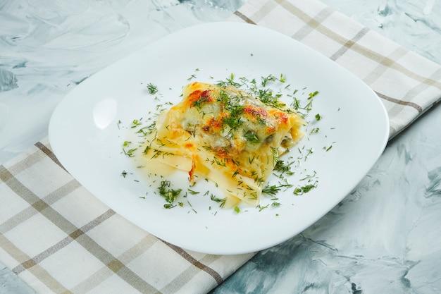 Część domowej włoskiej lasagne z serem, białym sosem i kurczakiem na białym talerzu z szmatką. tradycyjny włoski makaron. szary stół