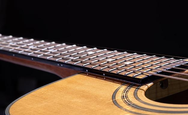Część gitary akustycznej, gryf gitarowy ze smyczkami na czarnym tle.