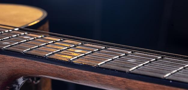 Część gitary akustycznej, gryf gitarowy ze strunami na czarnym tle z pasemkami.