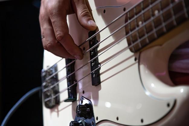 Część gitary basowej z bliska podczas gry na czarnym tle.
