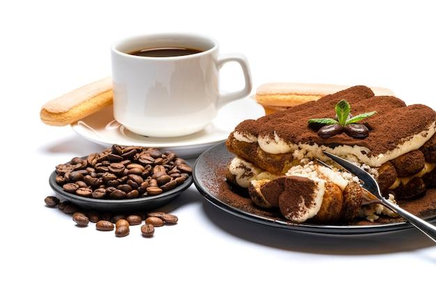 Część klasycznego deseru tiramisu, ciasteczka savoiardi i filiżankę świeżej kawy espresso na białym tle