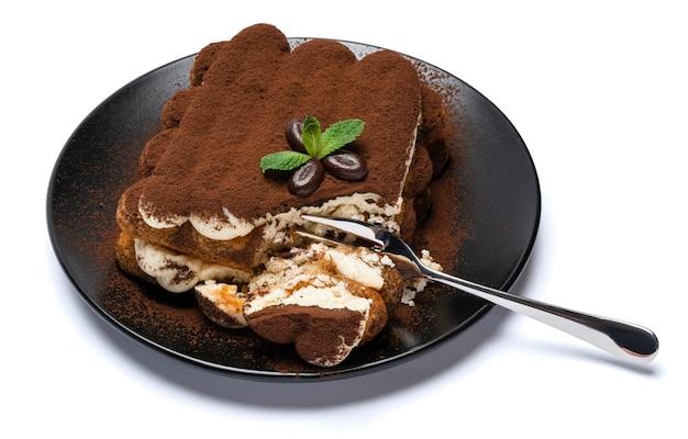 Część klasycznego deseru tiramisu na talerzu ceramicznym na białym tle
