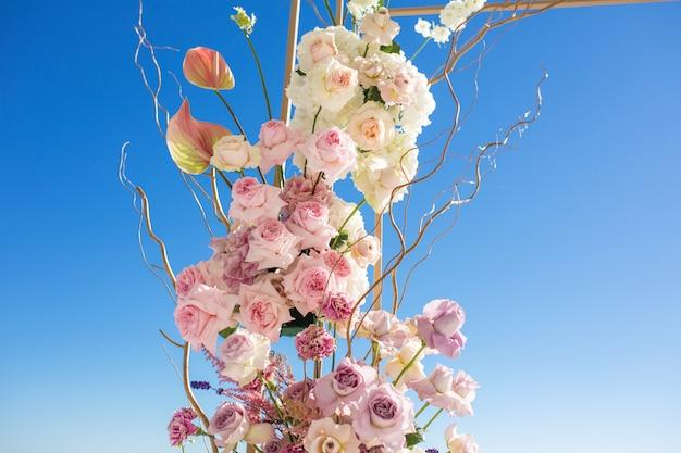 Część łuku ślubnego ozdobiona świeżymi kwiatami jest ustawiona na niebieskim niebie