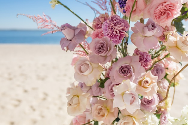 Część łuku ślubnego ozdobiona świeżymi kwiatami znajduje się na piaszczystym brzegu rzeki.