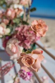 Część łuku ślubnego ozdobiona świeżymi kwiatami znajduje się na piaszczystym brzegu