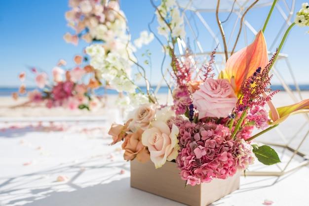 Część łuku ślubnego ozdobionego świeżymi kwiatami znajduje się na piaszczystym brzegu rzeki