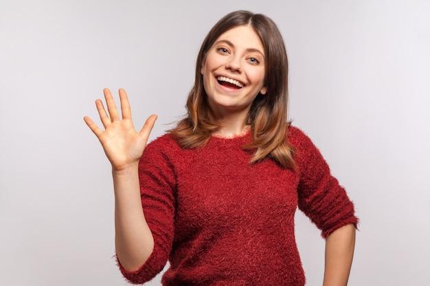 """Cześć miło cię poznać! portret szczęśliwej brunetki podnoszącej rękę, machającą """"cześć"""" i uśmiechającą się przyjaźnie"""