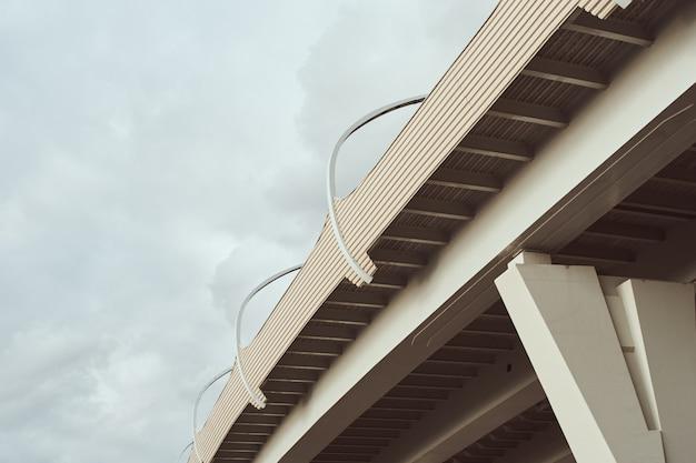 Część nowoczesnego mostu z ulicznymi światłami prowadzącymi przeciw chmurnemu niebu.