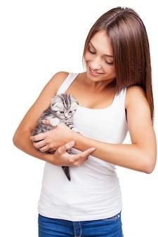 Cześć! piękna młoda kobieta trzyma małego kotka w rękach i patrzy na niego z uśmiechem, stojąc na białym tle