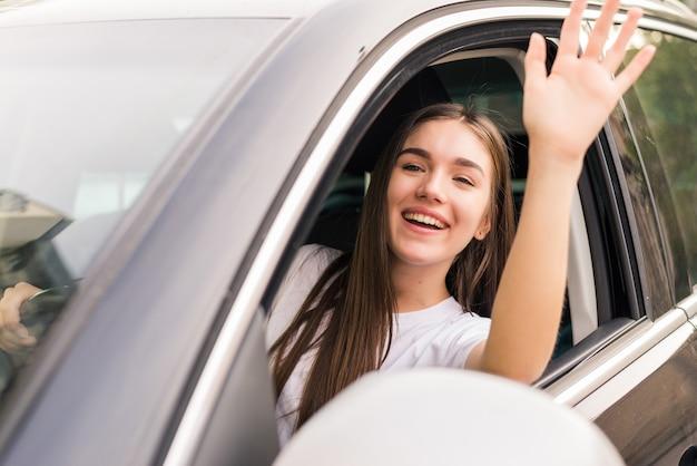 Cześć. piękne młode wesołe kobiety z uśmiechem i machając siedząc w swoim samochodzie