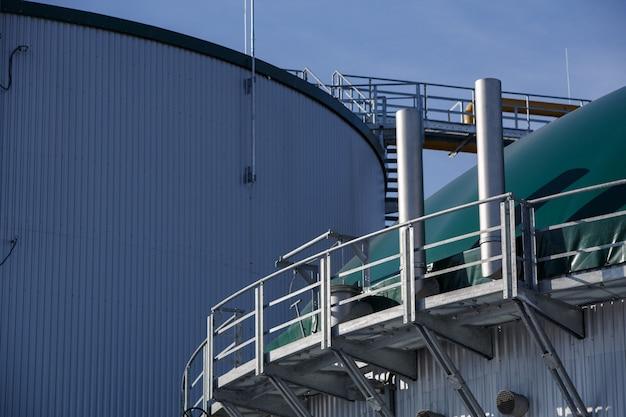 Część stalowych zbiorników przemysłowych na zewnątrz. dach metalowego budynku technologicznego w zakładzie przemysłowym na ścianie. sprzęt i urządzenia w firmie gazowej. metalowe schody drabiny na zbiorniku