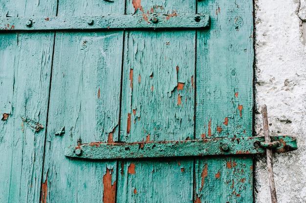 Część stare zielone drewniane drzwi w białej ścianie