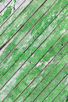 Część starej drewnianej ściany z desek pomalowanych na zielono, część farby, która się łuszczyła, zbliżenie