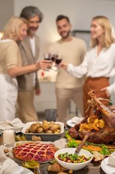 Część świątecznego stołu dziękczynienia podawanego z domowym pieczonym indykiem, sałatką, pieczonymi ziemniakami i słodkim ciastem na tle ludzi opiekających