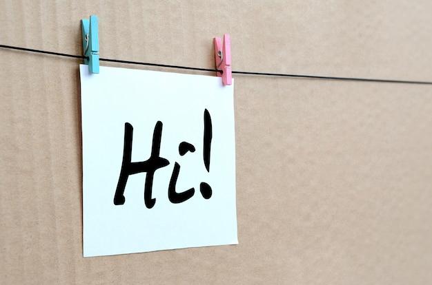 Cześć! uwaga jest napisana na białej naklejce, która wisi na spinaczu do bielizny