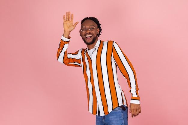Cześć! wesoły, przyjazny afro-amerykanin mówi cześć i macha ręką, pozdrowienie.