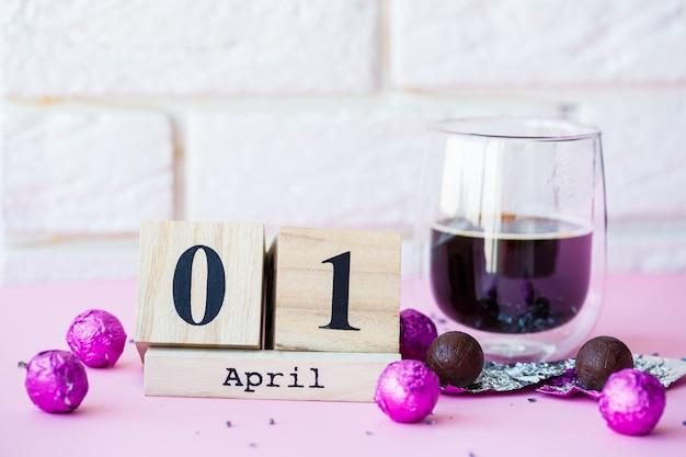 Cześć wiosna. drewniany kalendarz z datą 1 kwietnia, na różowym tle. światowy dzień śmiechu