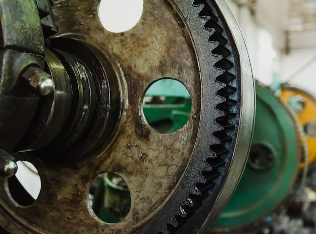 Część wirującej tokarki starej maszyny w fabryce. tokarki ślusarskie do produkcji części metalowych obiektów przemysłowych.