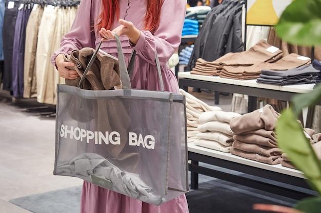 Część wizerunku kobiety, która wkłada zakupy do torby. sklep odzieżowy.