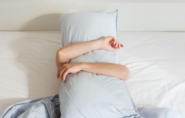 Część wnętrza domu lub hotelu, kobieta śpiąca rano na białym łóżku z niebieską pościelą, kobieta nakrywająca się poduszką