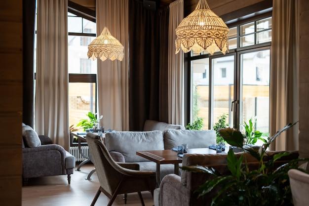 Część współczesnej luksusowej restauracji z drewnianymi stołami i wygodnymi kanapami między oknami