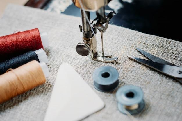 Część zabytkowej maszyny do szycia i element ubioru.
