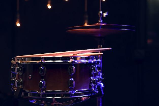 Część zestawu perkusyjnego w ciemności na niewyraźnym tle z boke.