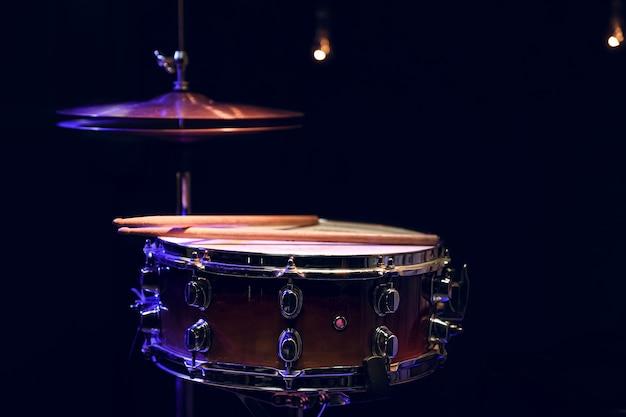 Część zestawu perkusyjnego w ciemności z pięknym oświetleniem. koncepcja koncertu i performansu.