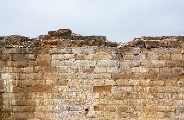 Część zniszczonego muru, wspaniała posiadłość. powierzchnia ma dekoracyjne wzory. cegły o różnych kształtach i rozmiarach.