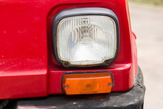 Części lampy przed czerwonym samochodem zabytkowym